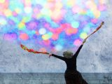 Photo by Sara Harley showing a woman reaching toward a sky of colourful spots of light.