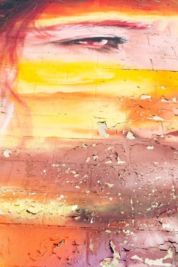 Photo by Justine MacDonald showing graffiti art of a woman's eye on an orange and yellow concrete wall.