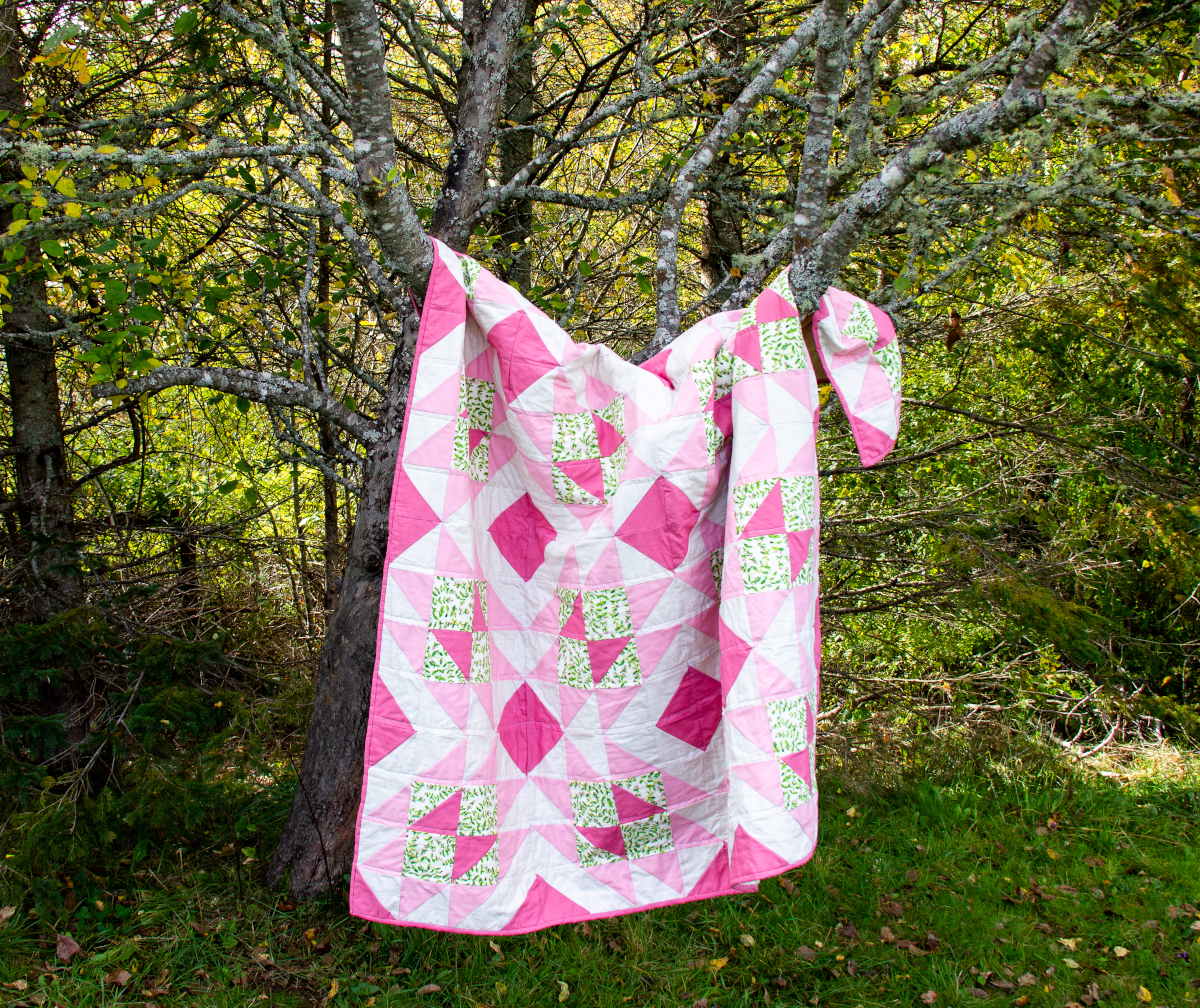 photo of a pik and green quilt hanging in a tree